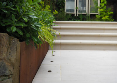 Wooden planters along grey steps with recessed lighting