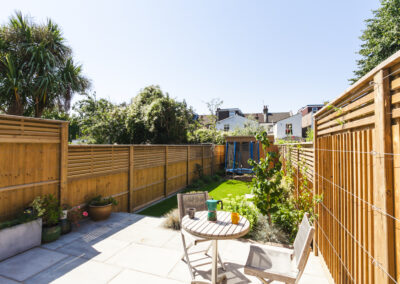Patio table and two chairs on grey tiles leading to family garden with lawn and shed