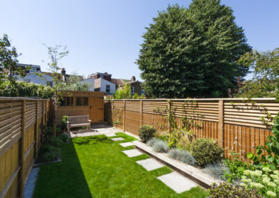 A lawn with paving leads to a wooden shed and wooden bench