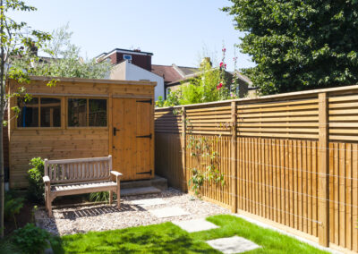 Wooden garden shed and wooden bench in a family garden with wooden fencing