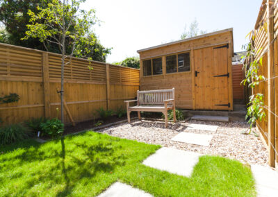Wooden outdoor shed and wooden chair in a family garden