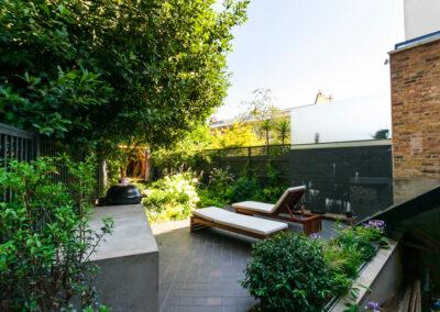 Kamado Joe barbecue and sun loungers in contemporary garden