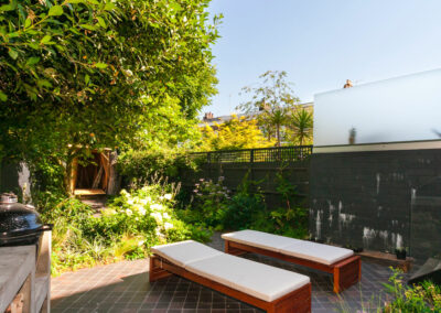 Two sun loungers and Kamado Joe barbecue in contemporary garden