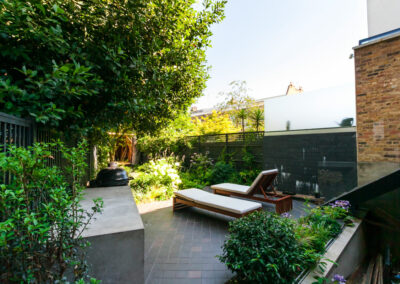 Two sun loungers on hand cut quarry tiles in contemporary garden