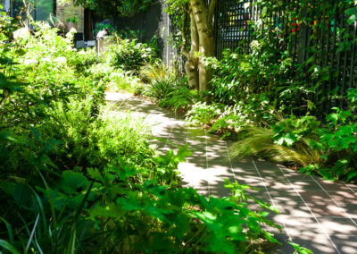 pathway with hand cut quarry tiles in a garden filled with plants
