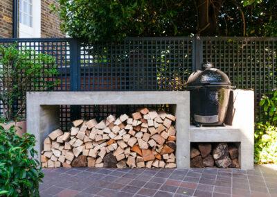 logs neatly stacked under Kamado Joe barbecue