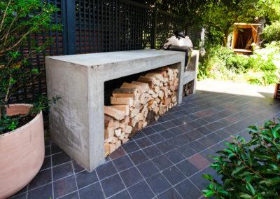 pile of logs beside Kamado Joe barbecue in contemporary garden