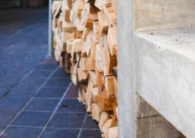 Logs piled neatly under Kamado Joe barbeque